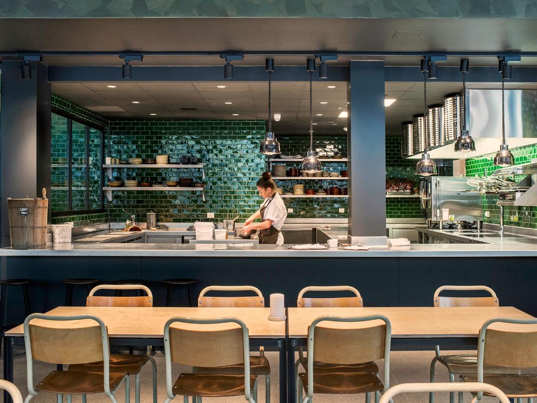 Fra sitteplassene i Jossa Mat og Drikke kan du se inn i det åpne kjøkkenet.