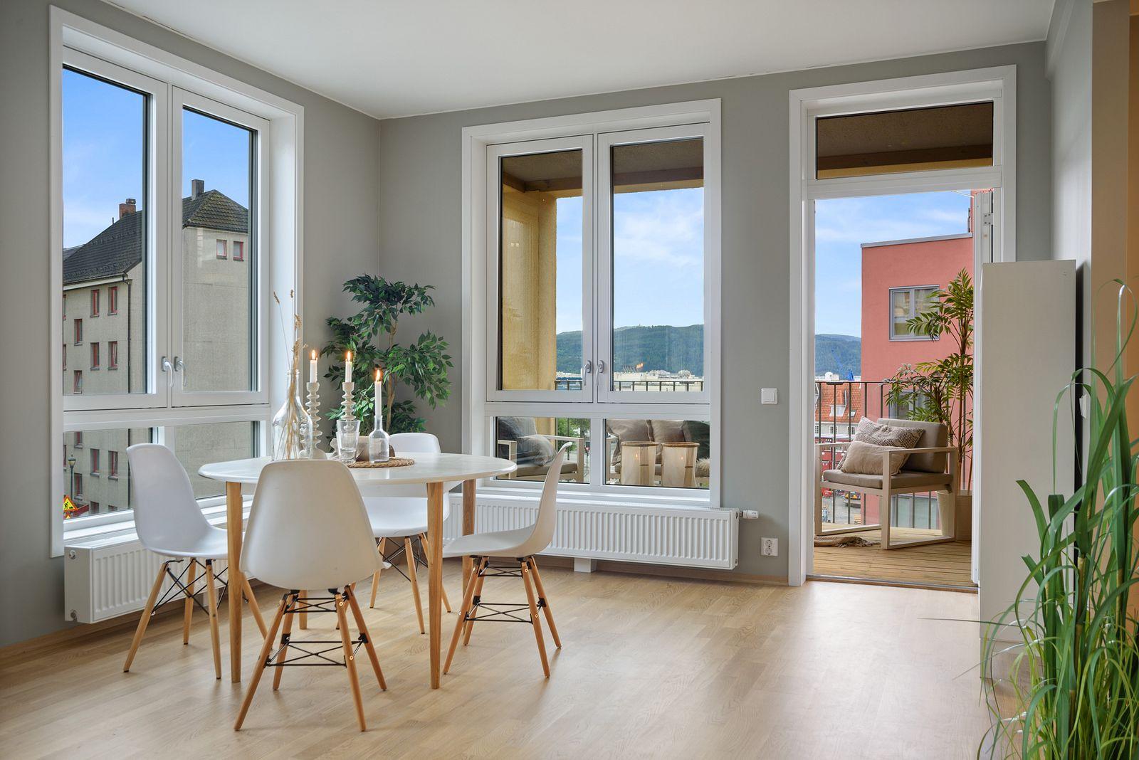 Romslig stue med god takhøyde, store vindusflater og mye lysinnslipp.
