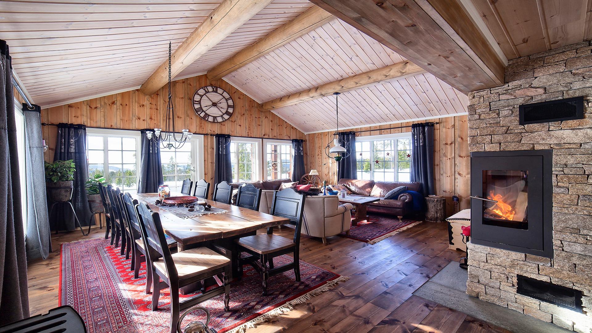 Ei stor og prangende stue med synlige stokker i taket.