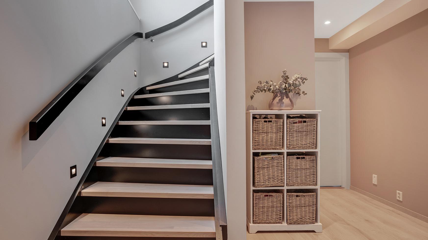 Den mørke trappa står i fin kontrast mot de lyse veggene